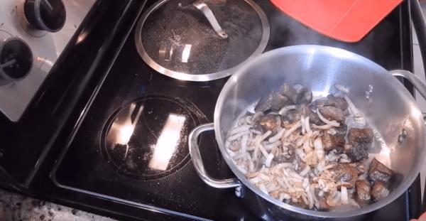 Ставим кастрюлю с мясом на огонь и выкладываем к нему лук.