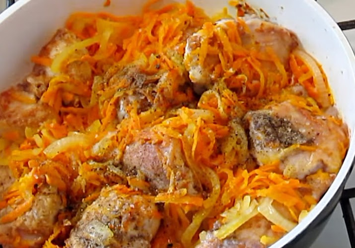 кролик с луком и морковью в сковороде