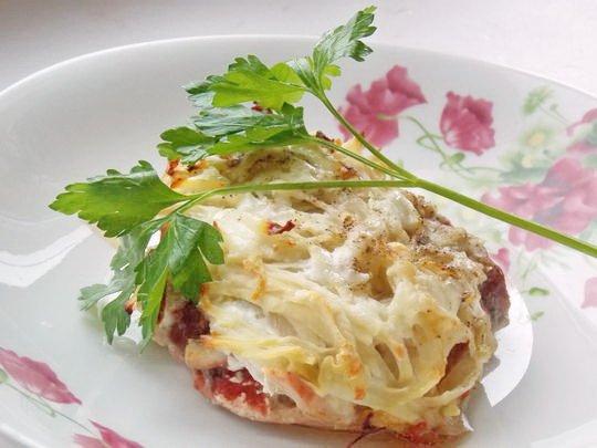 Мясо под картофельной шубой с веточкой свежей петрушки на тарелке