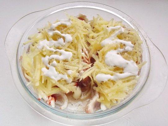 Мясо под слоем сырого тёртого картофеля со сметаной в стеклянной форме