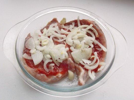 Мясо с кетчупом и полукольцами репчатого лука в стеклянной ёмкости